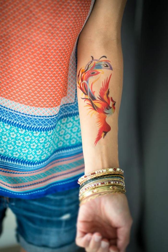 kleine tattoo ideen phönih vogel auf dem arm gemalt mit bunten farben viele armbänder bunt