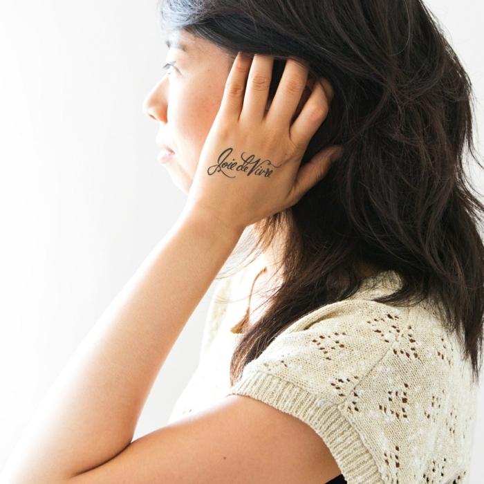 tattoo motive dezente idee für frauen schrift auf der hand schwarze haare spitze gestrickte bluse
