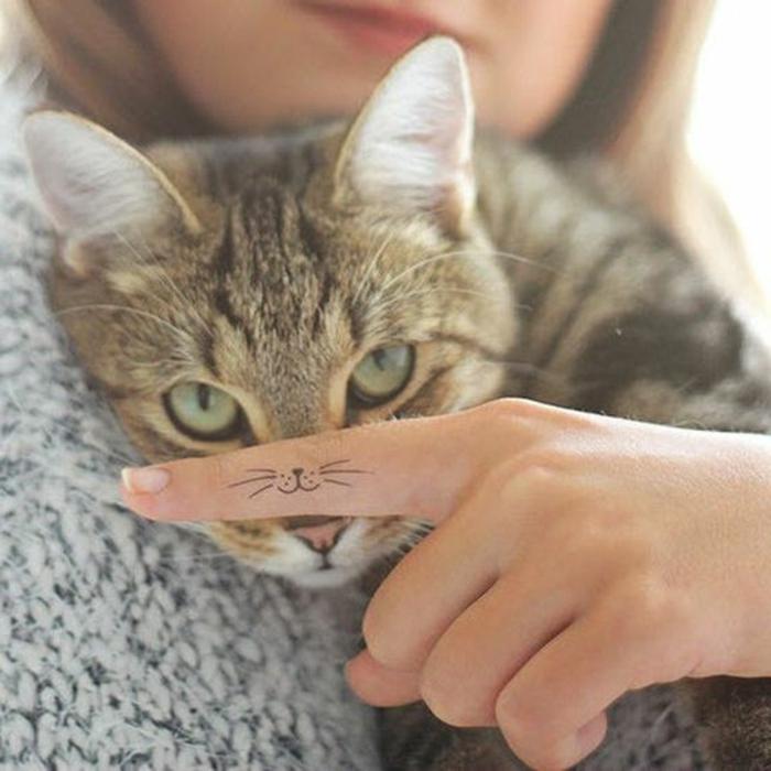 tattoo schulter frau katze mit grünen augen kleines dezentes tattoo weste nase tier kuscheln