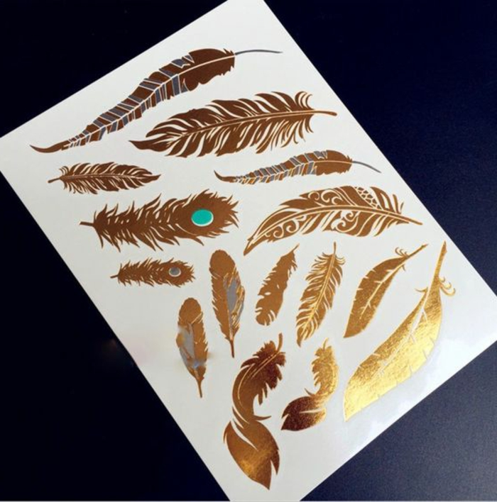 außergewöhnliche tattoos in goldener farbe feder türkis farbene dekoration tattoo inspiration