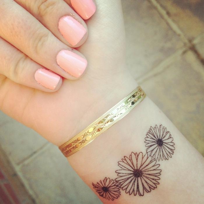 dezentes tattoo gestaltet in form von drei schönen kleinen blumen goldenes armband tolle maniküre