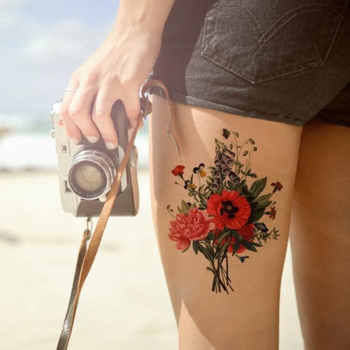 tattoos frau kamera shorts kurze hose blumen mohnblume blumenstrauß strand meer gefühl