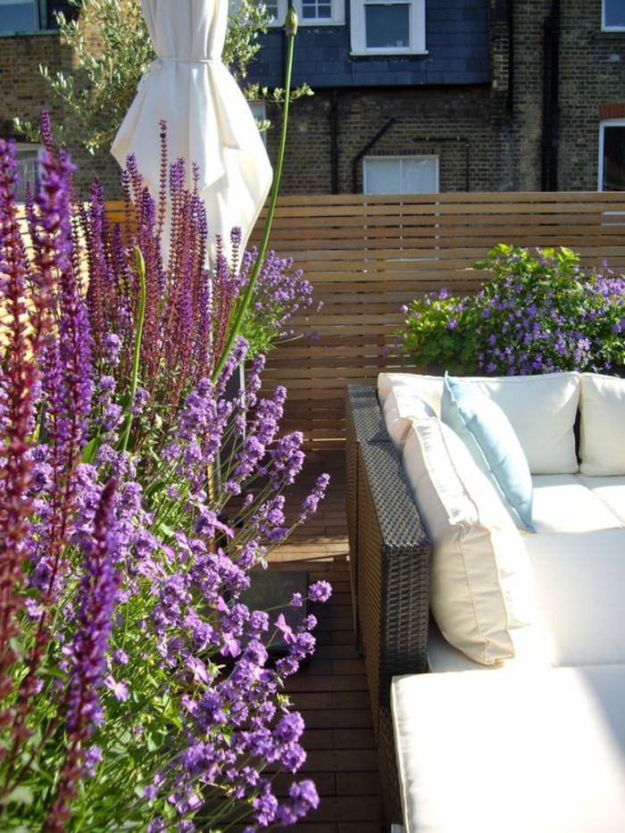 terrassengestaltung ideen sofa aus rattan weiße deko kissen weich bequem lavendel blumen lila
