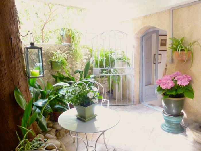 terrassen ideen geschlossene terrasse mit vielen blumen und anderen pflanzen rosa blume lampe