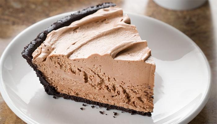 veganer Schokokuchen ohne Backen mit Schokoriegeln, Nüssen, Schlagsahne und Cookie Pie Crust