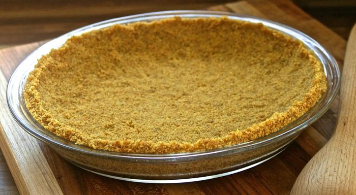 Schokokuchen Vegan - Cookie Pie Crust in einer Backform aus Glas auf einem Schneidebrett aus Holz