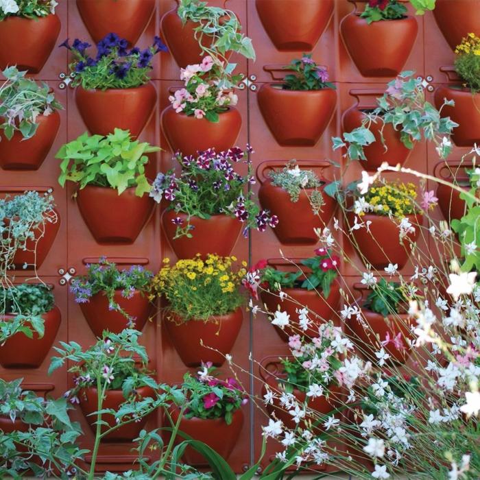 Pflanzenwand selber bauen - rote eingebaute Blumentöpfe aus Kunststoff
