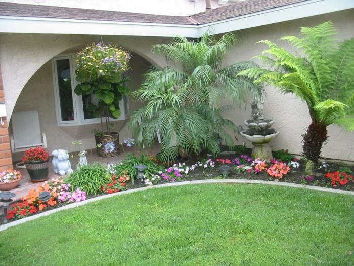 Palmen, Brunnen und hängende Blumentöpfe und Gartenfiguren - schöne Vorgarten