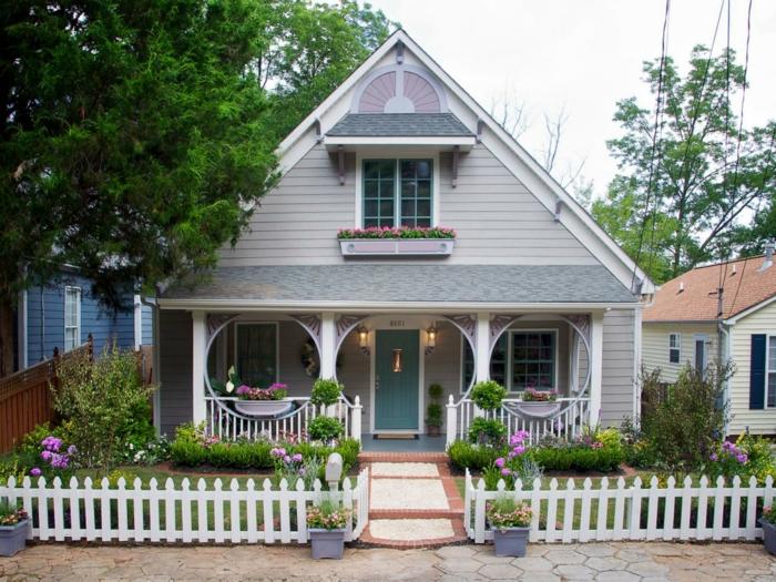 Haus mit gerundeten Motiven - symmetrische Gestaltung und weißer Zaun - moderner Vorgarten