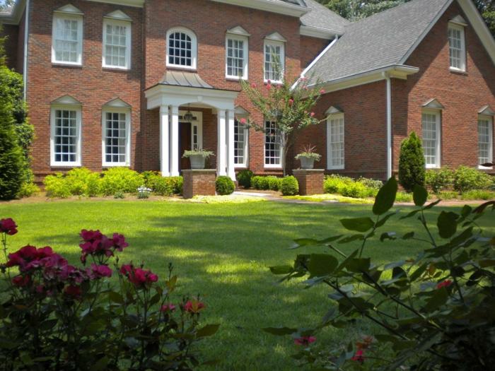 symmetrischer moderner Vorgarten - Rasen, Hecke und lila Blumen