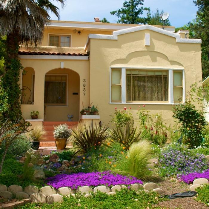 lila Blumen, Zierstrauche vor einem gelben Haus - schöne Vorgärten