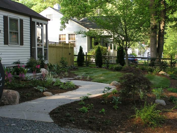 kleine Bäume, Blumenbeete, graues Pfad Vorgartengestaltung mit Kies