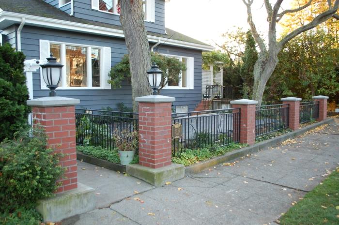 kleiner Vorgarten mit dicken Bäumen und Laternen - ein Eimer mit Pflanzen