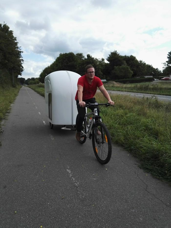 hier ist ein radfahrer auf derm weg mit einem weißen fahrrad wohnwagen