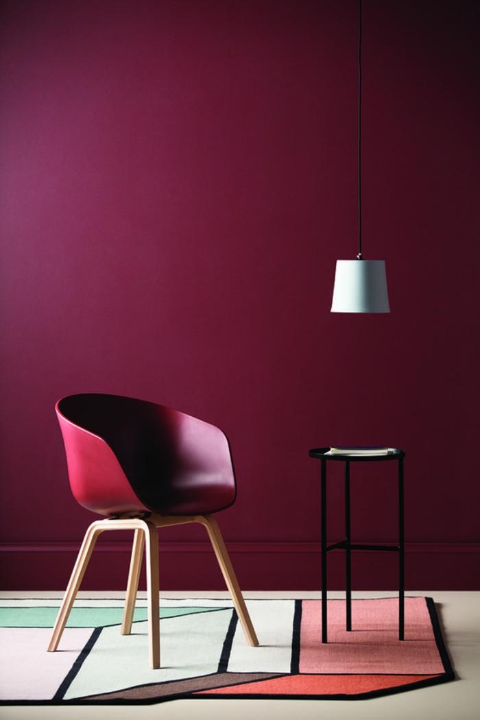 weinrote Wand, farbiger Musterteppich mit geometrischen Figuren, weinroter Plastikstuhl, hängende Lampe