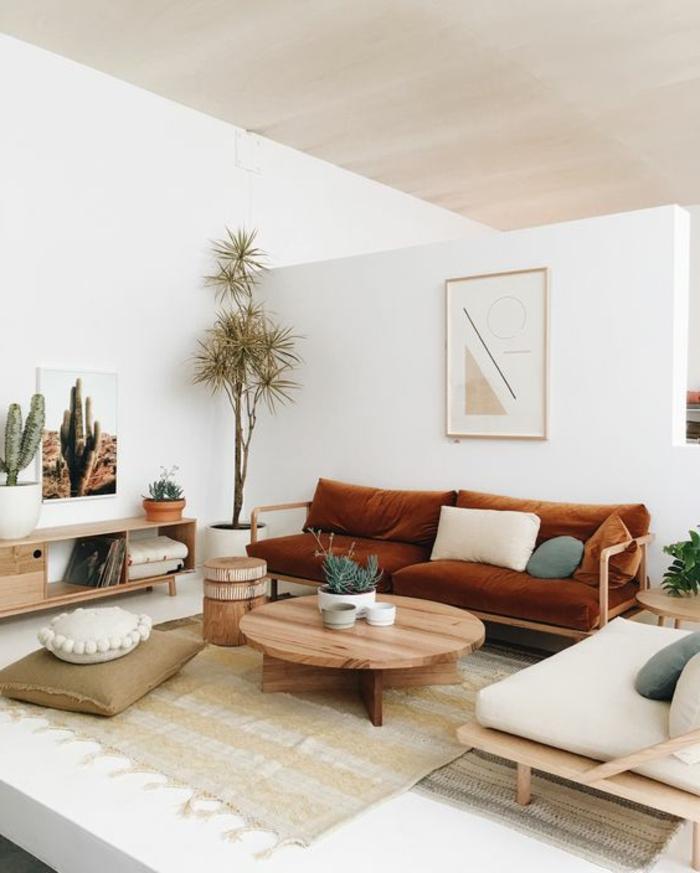 braune Polstercouch und weißer Sessel, runder Couchtisch aus Holz, Holzhocker, Musterteppich, Kaktus