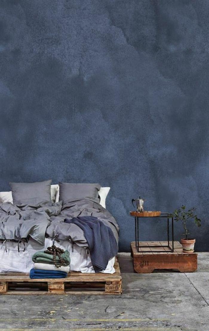 Schlafzimmer mit grau-blauer Wand, Doppelbett aus Europaletten, graue Schlafdecke