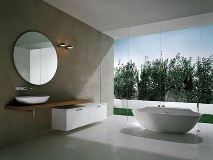 Badezimmer mit rundem Spiegel, Schrank in weißer Farbe und weiße ovale Badewanne, Waldaussicht
