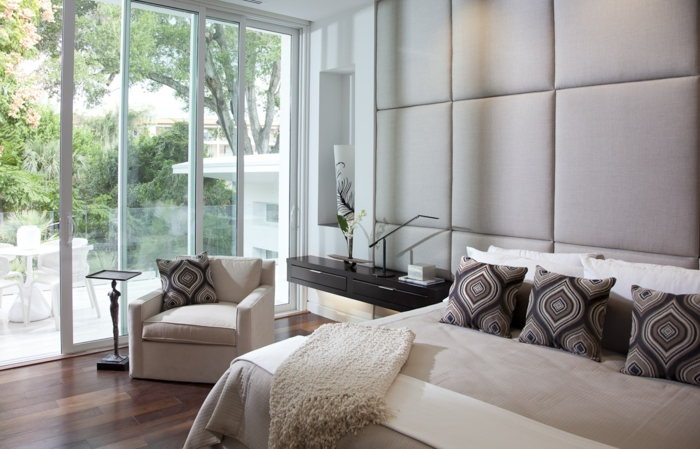 Wandverkleidung, Doppelbett mit Musterkissen, weißer Sessel mit Beistelltisch, Terrasse mit Schiebetür