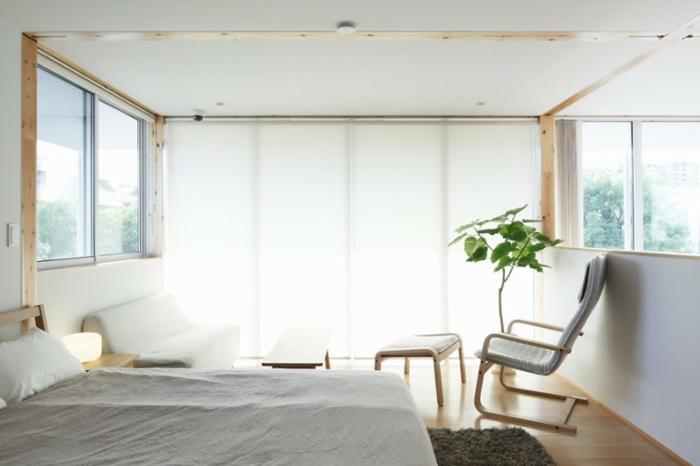 Schlafzimmer mit weißer Couch, Relax-Stuhl mit weißer Hocker, Doppelbett mit weißer Schlafdecke