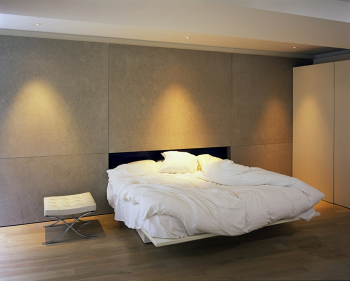 minimalistisches Schlafzimmer in Naturfarben mit Doppelbett mit weißen Lacken, Lederhocker in Weiß, Led-Licht