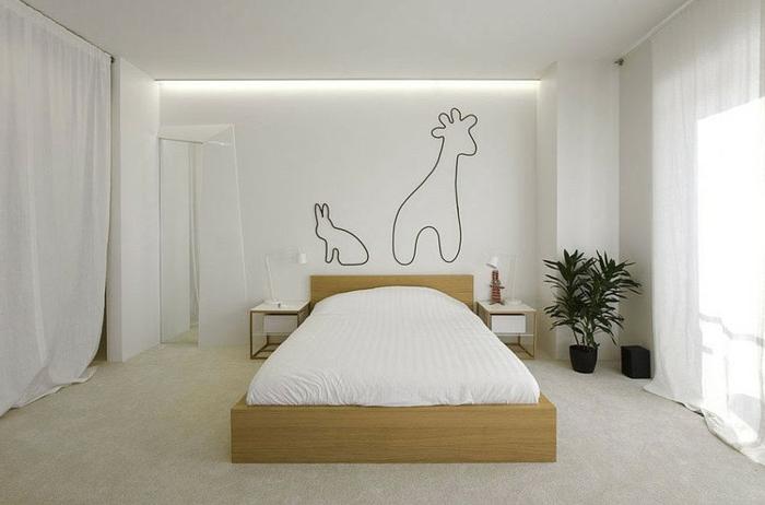 weiß gestrichenes Schlafzimmer mit Holzbett, langen weißen Gardinen und einfachen Zeichnungen an der Wand