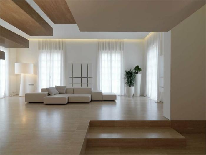 Wohnzimmer in Naturfarben mit weißer Couch, zwei Pflanzen, Designer-Stehlampe und Laminatboden