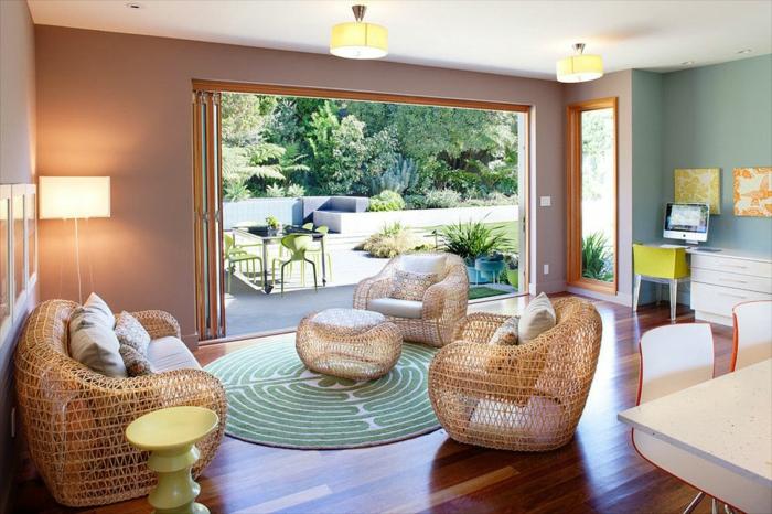 ein großes Wohnzimmer mit rundem Musterteppich in türkisgrün und weiß, großer Garten