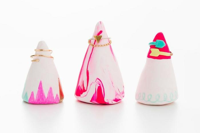 ringständer aus rosa und weißem ton dekoriert mit farbstiften, goldene ringe