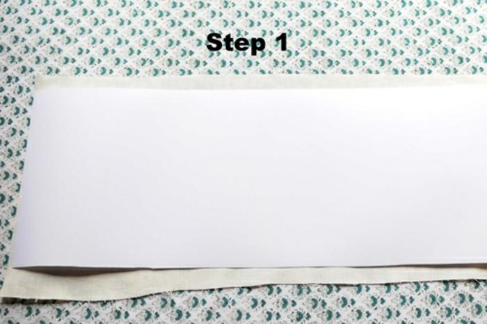 Lampenschirme selber basteln: ein Blatt weiße Aufklebfolie, ein Stück grau-grüner Nähstoff, Basteltisch