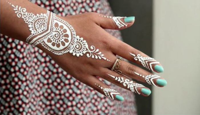 Henna Farbe: weißes Henna, Frau mit buntem Kleid mit Tattoo am Finger und Tattoo am Handgelenk