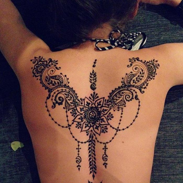 Frau mit tätowiertem Rücken, schwarzes Mandala Tattoo am Rücken, schwarz-weißer Badeanzug für Frauen