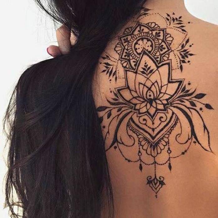 Frau mit langen dunklen Haaren mit schwarzem Rückentattoo unter dem Hals, Lotusblume aus Henna