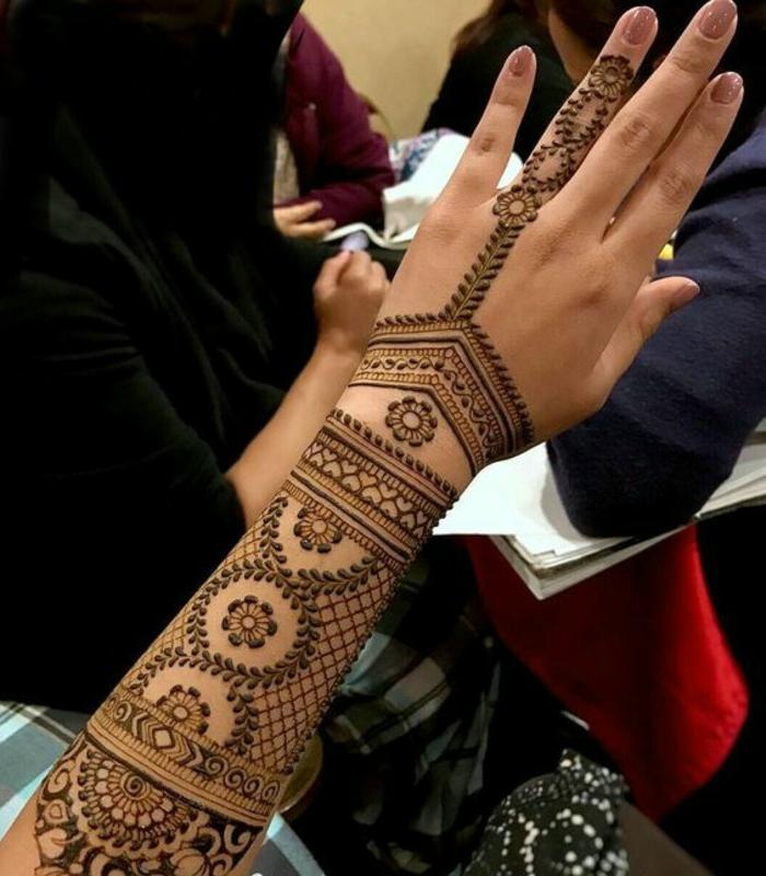 Frauentattoos am ganzen Arm und am Unterarm mit vielen kleinen Ornamenten aus Henna Farbe, Ringfinger Tattoo