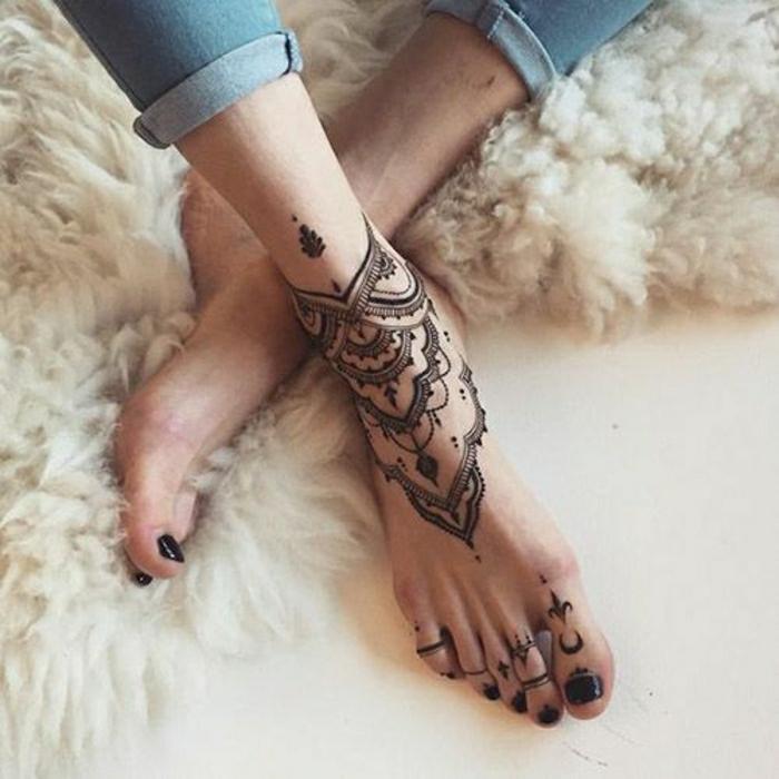schwarzes Knöchel- und Zehentattoo, Frau mit Jeans und schwarzem Nagellack auf den Zehen