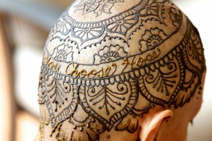 eine Frau mit schwarzem Kopftattoo aus Hennafarbe, goldene Buchstaben, florale Motive