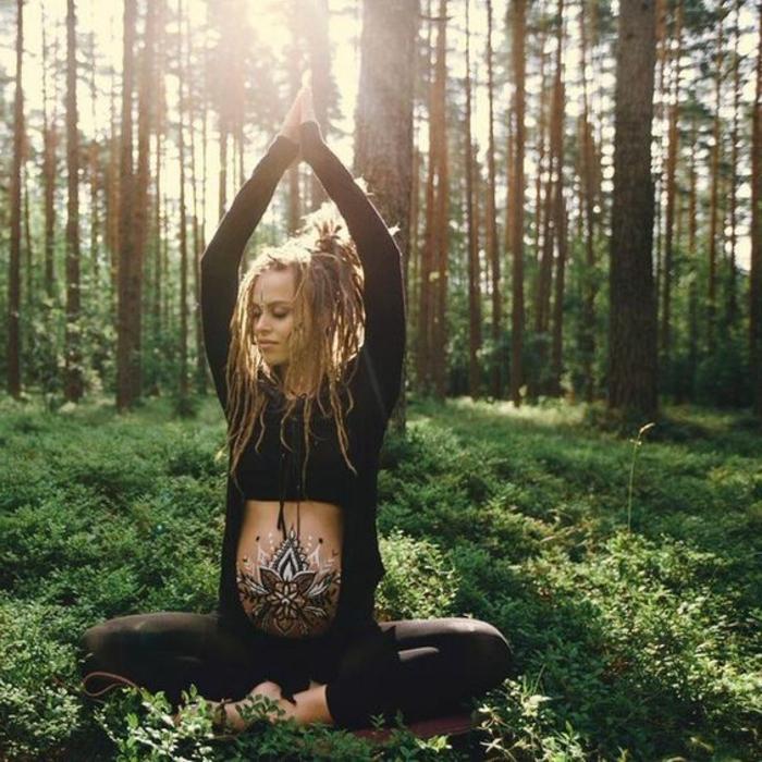 Yoga im Wald treiben, Frau mit blonden Haaren mit Rastafrisur, Rastazöpfe, schwangere Frau in schwarzer Sportkleidung