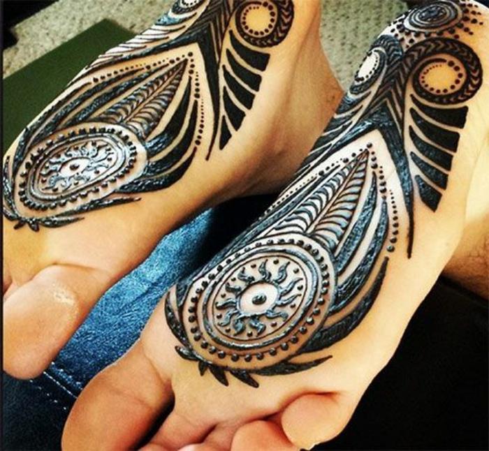 Fußtattoo auf der unteren Seite beider Füße, Sonnentattoo, schwarzes Tattoo mit vielen Linien und Punkten