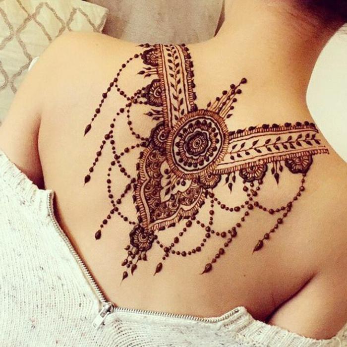 rötliche temporäre Tätowierung mit Henna Farbe am Rücken einer Frau unter dem Hals, Punktentattoo