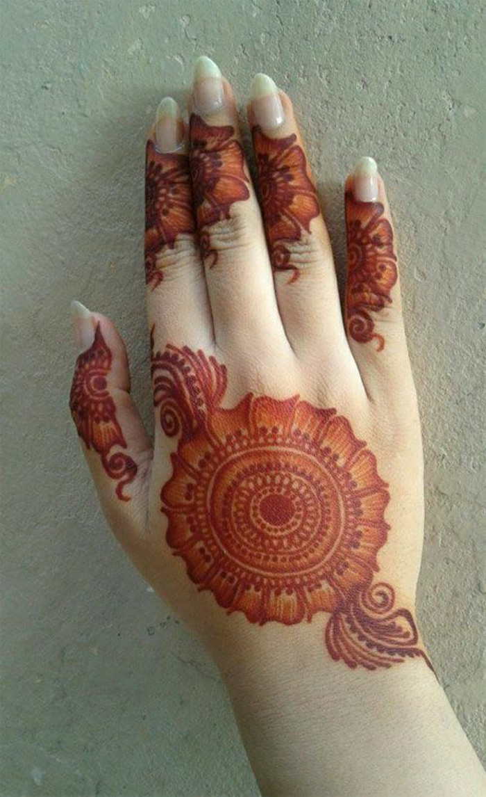 temporäre rote Henna Tätowierung auf der Handoberfläche einer Frau mit langen Nägeln, Blumentattoos
