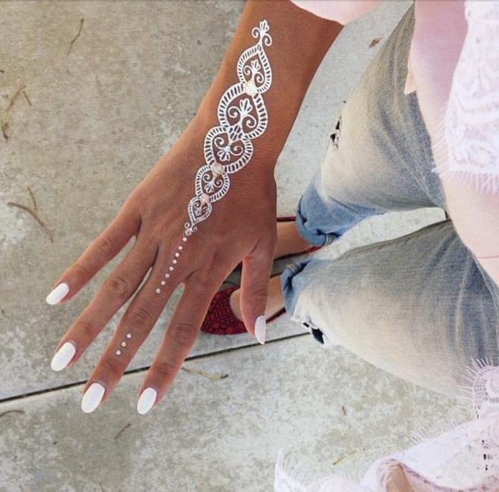 weißes Arm- und Handoberflächentattoo mit kleinen Punkten, weiße Nägel, Jeans, hellpinke Bluse, pinker Schal