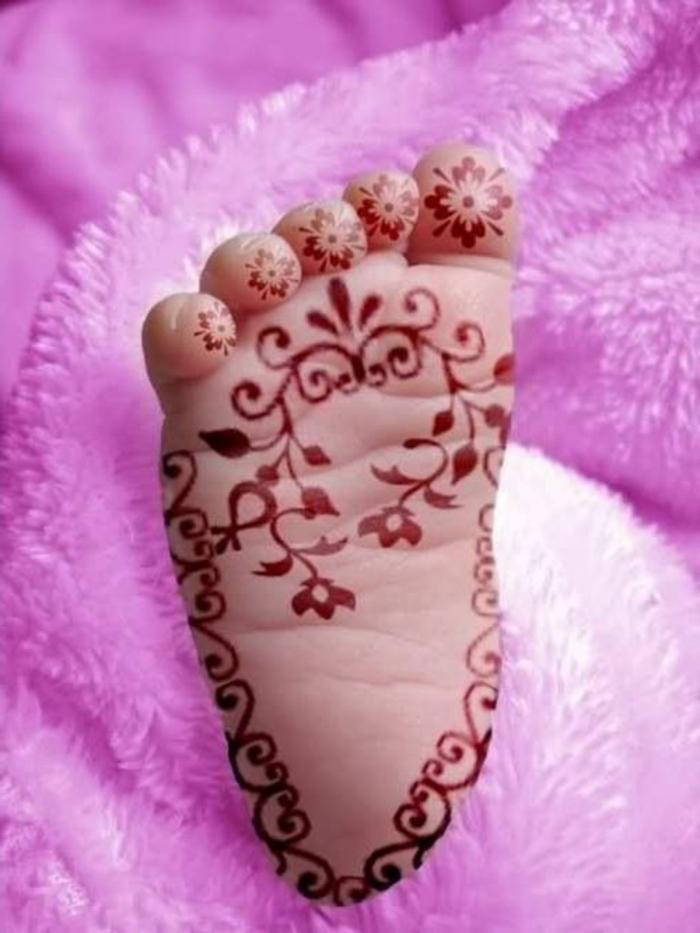 ein Babyfuß mit Tattoo aus roter Henna Farbe, Zehentattoo für Babys, florale Motive, pinke Plüschdecke