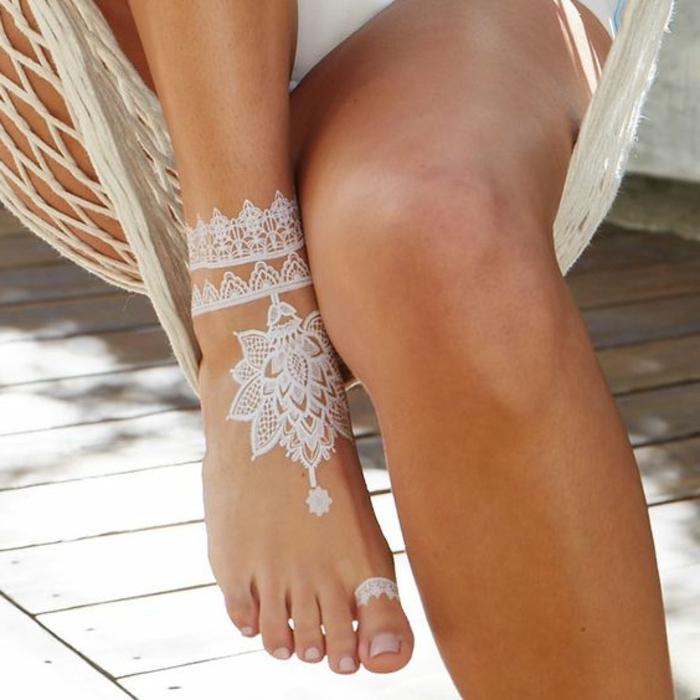 ein schönes Knöcheltattoo aus weißem Henna, Ringtattoo auf der großen Zehe einer Frau, Hängestuhl