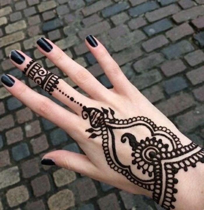 Frau mit Henna Tattoo auf der Hand und auf dem Mittelfinger in schwarz, schwarzer Nagellack