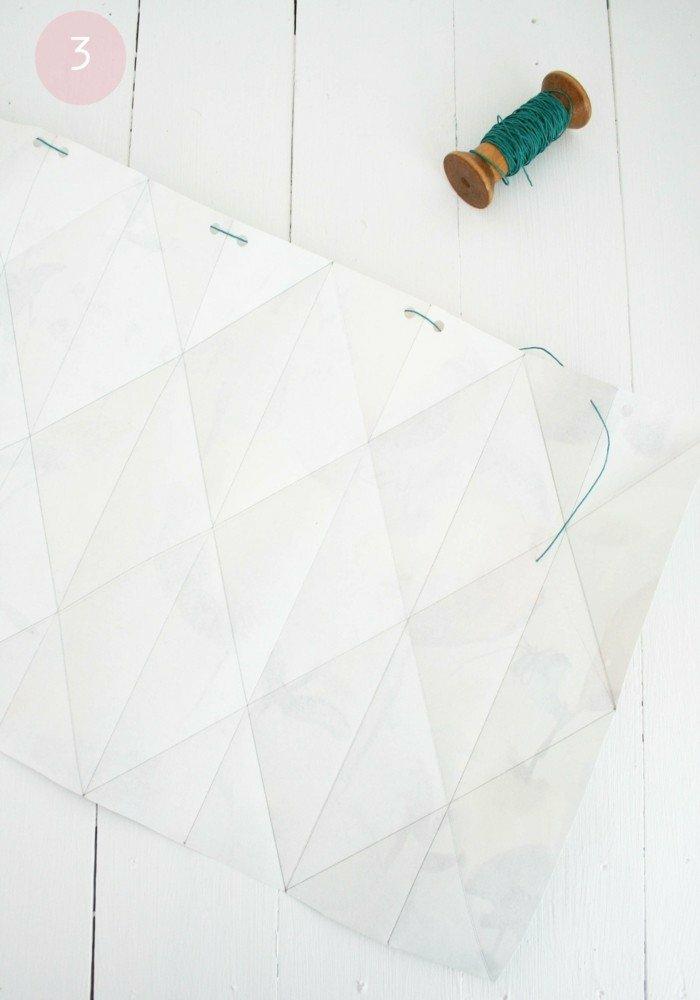 Lampe selber bauen - gefaltetes Bastelpapier mit kleinen runden Löchern an den Kanten und ein eingenähten Faden
