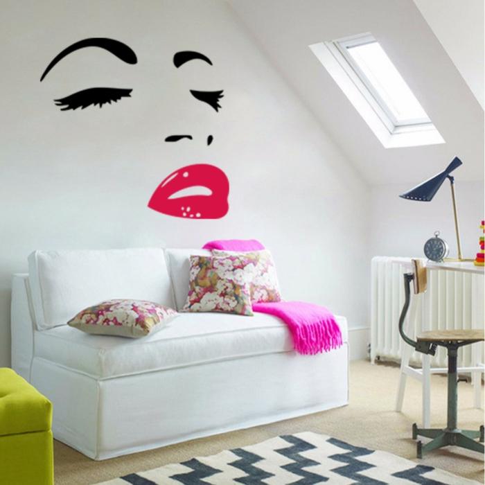 ein Gesicht Wandtattoo über weißem Sofa mit bunten Kissen Teppich mit geometrischem Muster Rockabilly Deko