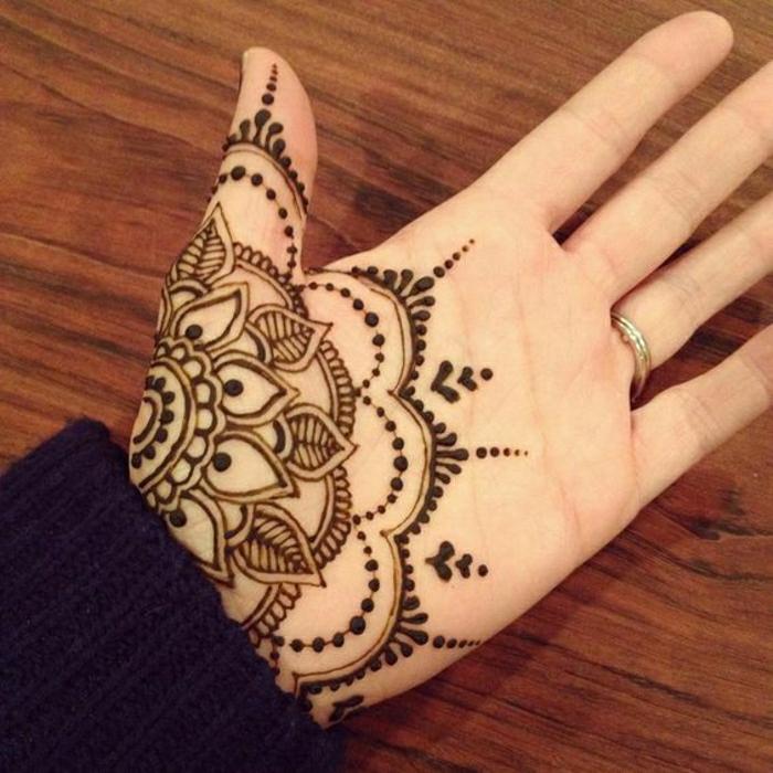 ein schwaz-rötliches Tattoo mit Hennafarbe auf der inneren Seite des Handes, Hand mit Ehering