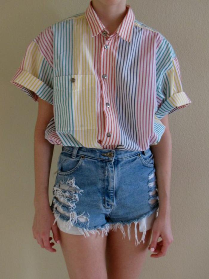 ein Mädchen mit einem oversized Hemd mit Streifmuster, Pastellfarben, zerrissene kurze Hose aus Denim