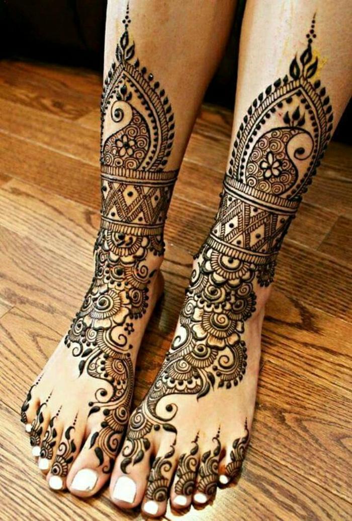 Frau mit tätowierten Beinen, Knöcheln und Zehen mit Hennafarbe, viele Ornamente, weißer Nagellack