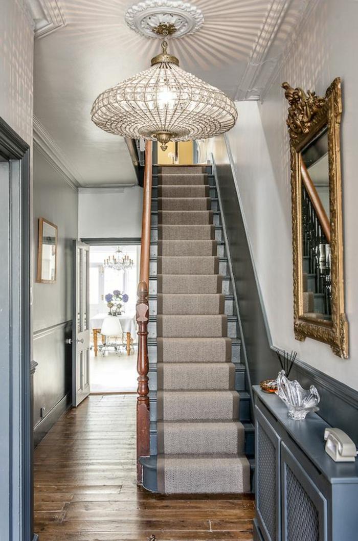 wunderschöner Kronleuchter und antike Treppe mit Textilbelag